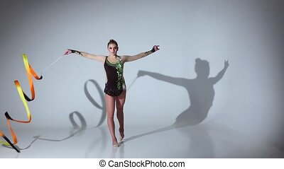 Rhythmic gymnast doing acrobatic moves with the tape. White...