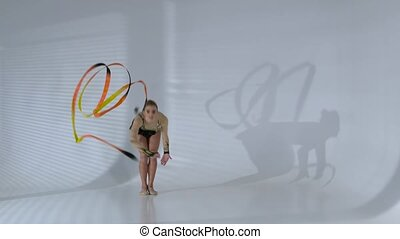 Rhythmic gymnast gracefully dancing with a ribbon in his hands. White background