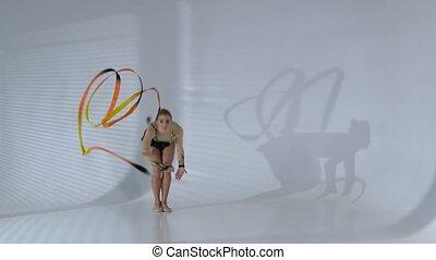 Rhythmic gymnast gracefully dancing with a ribbon in his...