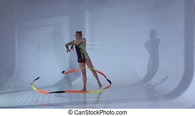 Rhythmic gymnast gracefully dancing with a ribbon in his hands. White background. Slow motion