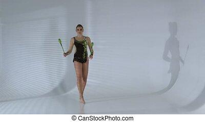 Rhythmic gymnast kneeling and holding her mace it makes...