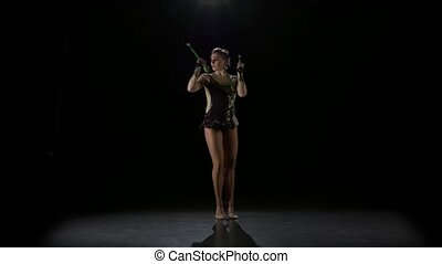 Rhythmic gymnast throws mace up and catches her. Black background