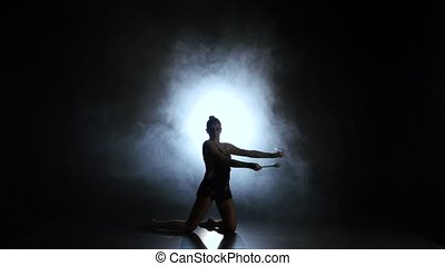 Rhythmic gymnast throws mace up and catches her. Black background. Light rear. Silhouette