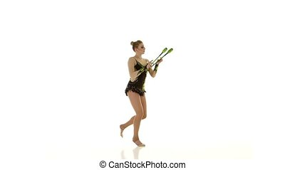 Rhythmic gymnast throws mace up and catches her. White background