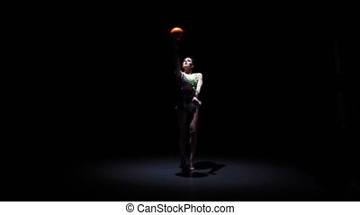 Rhythmic gymnast with a ball moves beautifully. Black background. Slow motion