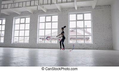 Rhythmic gymnastics: Girl in black body perform gymnastics exercise with a colored ribbon in sport school near big windows. Ballet School