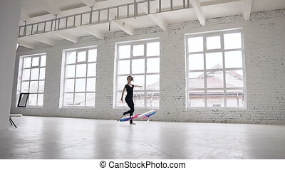 Rhythmic gymnastics: Girl in black body perform gymnastics exercise with a colored ribbon in sport school in windows background at gymnastics school. Ballet School. Workout
