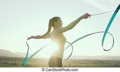 Rhythmic gymnastics: Girl in sport bodysuit perform gymnastics exercise with a blue ribbon on outdoor at sunset or sunrise. Gymnastic workout