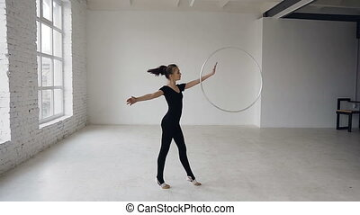 Rhythmic gymnastics: gymnastic girl dressed black bodysuit performs training a gymnastics exercise with a hoop at sport school