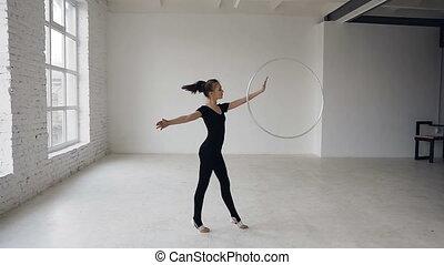 Rhythmic gymnastics: gymnastic girl dressed black bodysuit performs training a gymnastics exercise with a hoop at sport school