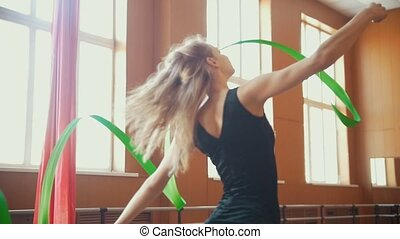 Rhythmic gymnastics - young woman training a gymnastics exercise with a green ribbon, slow-motion
