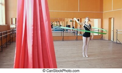 Rhythmic gymnastics - young woman training a gymnastics...
