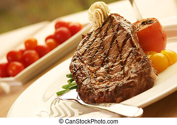 12oz ribeye steak topped with truffle butter and grilled tomato. Shallow DOF.