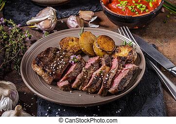 Rib eye steak with herbs, roasted potatoes, hot tomato...