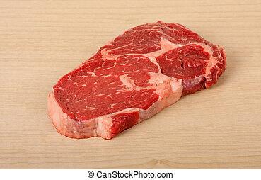 Uncooked piece of rib eye steak on a cutting board