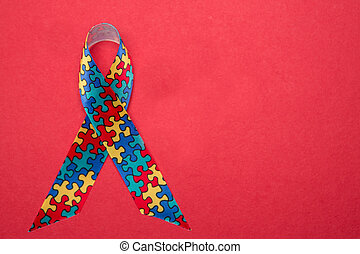 Ribbon for autism and aspergers awareness with copy space on red background