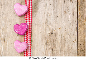 Ribbon with hearts on a rustic wooden background