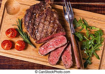 Ribeye steak with arugula and tomatoes. - Ribeye steak with...
