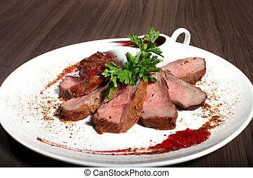 Ribeye steak with arugula on dark wooden background.