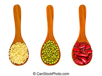 Rice and beans in wooden spoons on white background
