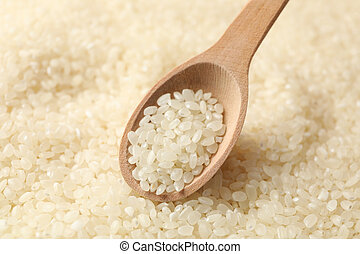 Rice background and wooden spoon, close up