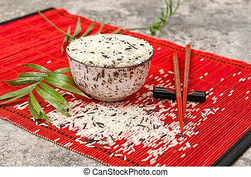 Rice bowl chopsticks red bamboo mat background Asian cuisine