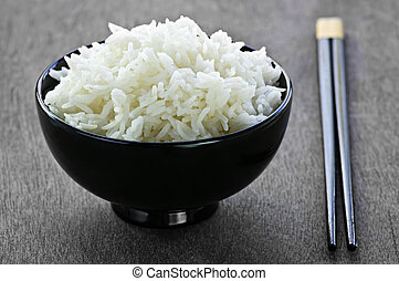 Rice bowl with chopsticks - White steamed rice in black...