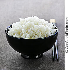 White steamed rice in black round bowl with chopsticks
