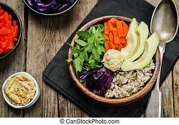 Rice bowl with red cabbage, carrots, avocado, arugula and hummus