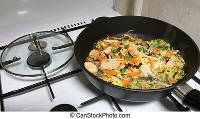 Rice chicken breast and vegetables on a frying pan