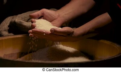 Rice falling from hands. Raw groats pile. Natural food high...