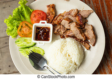 Rice, fried pork with vegetables on a white plate.