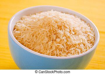 Rice grain in bowl - Raw rice grain in bowl on yellow...