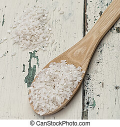 Rice grains are in a wooden spoon