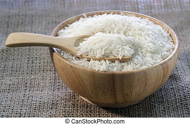 Rice in a wooden bowl on sackcloth background
