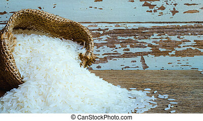 Rice in bag on wooden background