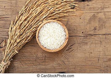 Rice in bowl with rice paddy on rustic wooden background