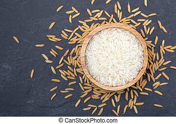 Rice in wooden bowl on dark stone background