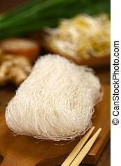 Rice Noodles - Raw rice noodles on wooden board with...