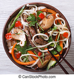 rice noodles with mushrooms , meat, vegetables close-up top view
