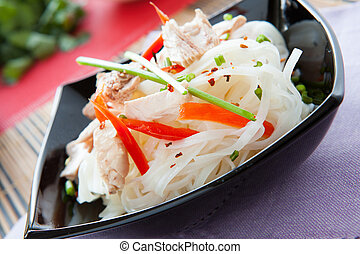 rice noodles with peppers and tuna in a black bowl