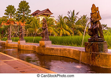 Rice plantation and statues during a sunset in Ubud, Bali, Indonesia