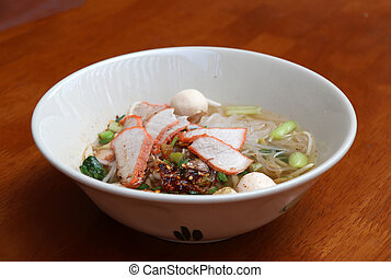 Rice stick noodles soup with red roasted pork in the bowl on the wooden table.