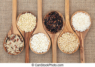 Rice varieties in olive wood spoons over hessian background.