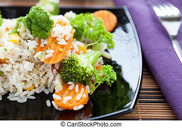 rice with carrots and broccoli on a black plate