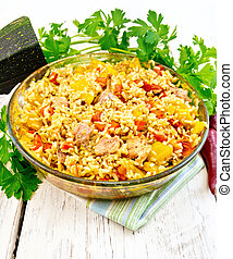 Rice with chicken and zucchini in glass pan on board