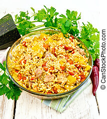 Rice with chicken and zucchini in pan on light board