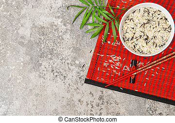 Rice with chopsticks red bamboo mat background