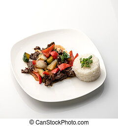 Rice with garnish and salad. Food plate isolated on white background. Organic nutrition cuisine. Top view. Appetizer dish from restaurant menu. Exquisite served dish