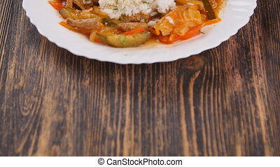 rice with meat and vegetables on wooden table - rice with...